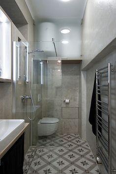 Sprchový kout byl navržen pouze s vyspádovanou podlahou. Od zbytku koupelny ho dělí jenom čiré sklo, což opticky daný prostor zvětšuje.