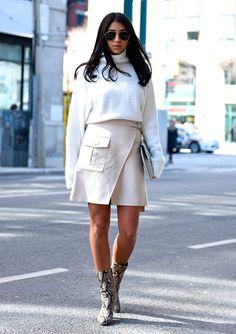 Street style look com blusa manga longa branca, saia tranbspasse e fenda frontal e bota com estampa cobra.