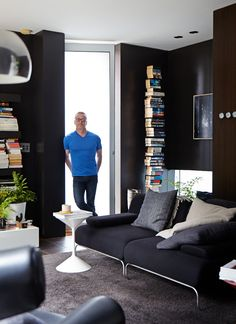 Paul Hecker at home.  Downstairs loungeroom - Ox chair (soft focus in foreground), white side table by Zanotta, Arco lamp.  Photo - Sean Fennessy, Production – Lucy Feagins / The Design Files.