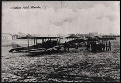 """1917-1918 -- Mineola --Hazelhurst Field """"Aviation Field, Mineola, L.I."""" """"U.S. Air Service, World War I, Mineola, Long Island, line-up of De Haviland DH airplanes."""" A line of US Army Air Corps Dayton Wright DH-4 biplanes on the line at Mineola Field, Long Island, New York, circa 1917-1918. Hangars in background, small crowd in right foreground."""