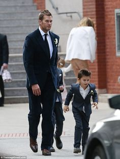 Looking good: The Patriots star walked with his sons John and Benjamin