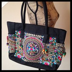 "Hmong Thai style embroidered bag NWOT Beautiful, roomy bag, featuring multicolored embroidery all the way around the outside, and beaded tassels. Approximate measurements are: 18"" in length, 12"" in height and just under 6"" wide (not including handle). Bag closes with zipper. Inside is one zippered pocket, and an open pocket on the other side. Straps are thick and durable. Additional photos can be posted on request! Boutique Bags"