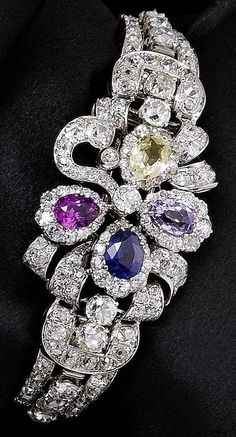 A sapphire and diamond bracelet, circa 1930. The central design is of a flowerhead motif with old brilliant-cut diamond foliate scrolls, each petal alternately set with a pear-shaped sapphire of varying hue, including pink, yellow, blue and purple, the detachable tapered strap composed of overlapping old brilliant-cut diamond semi-circular links with similarly cut diamond highlights, centre piece can be worn alone as a clip brooch, originally part of an earlier 19th century jewel.