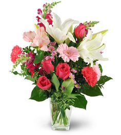 """If ever there was the perfect bouquet with which to say """"I Love You,"""" our Love Blooms would take the cake! Bubbling over with white oriental lilies, feisty snapdragons and lively pink and red roses, this bouquet will touch the heart of that special someone like no other - or make that birthday one to remember! This lush and lovely arrangement comes in an elegant glass vase - a gift in itself!"""