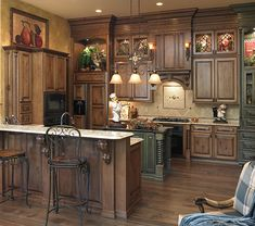 Perimeter Cabinets: Acorn Rustic Maple w/ Black Glaze, Oxford door style; Other: Sea Green Maple w/ Black Glaze, Oxford Special Features: Turned Leg 8 on island, wood refrigerator panels, bead-back wall cabinets, stacked cabinets, Oxford bar back with Enkeboll corbels mounted on 6