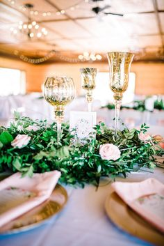 Mercury glass candle holders surrounded by greenery for pretty rustic wedding detail