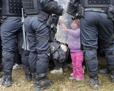A young girl touches the riot shield of a police officer after crossing the border from Croatia, in Rigonce, Slovenia 2015.