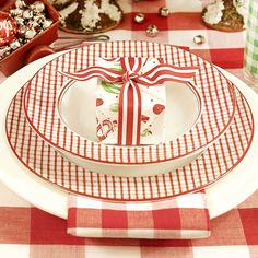 Red-and-White-Check Table Setting: Mix everyday dishware with inexpensive decorative accents for a table. Layer a red-and-white-check napkin between a basic dinner plate and a festive salad plate. A small gift-wrapped box containing a sweet treat punctuates each place setting of red-and-white dishes.