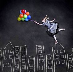 Girl in black white apron holding balloons with chalk drawing of skyline art