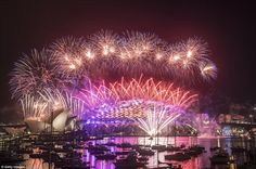 Happy New Year! Pink, purple and orange fireworks explode over the Sydney Harbour Bridge a...