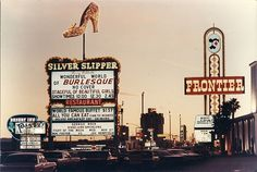 "Marquees of the Silver Slipper, Desert Inn and Frontier Hotels in Las Vegas, Nevada, at twilight. The Sands Hotel tower can be seen in the distance. (The Silver Slipper marquee advertising the ""Fight of the Week"" between Mac Foster and Joe ""Hempfield"" was supposed to read Joe Hemphill.)"