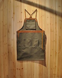 Workman's apron with a stylish leather trim, and criss-crossing strap in the back.