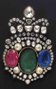 A DIAMOND, EMERALD, RUBY, SAPPHIRE, AND CULTURED PEARL BROOCH  Centering upon an oval-cut emerald, flanked on either side by an oval-cut ruby or sapphire, spaced by four cultured pearls, each accented by diamond collets, to the vari-cut foiled and openback diamond panel of openwork design, surmounted by a pear-shaped rose-cut diamond within a foiled surround, mounted in silver and gold, (with single-cut diamond pendant hoop for suspension, one diamond deficient)