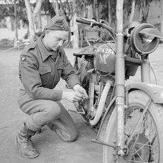 The British Army in North Africa 1944: Driver A Beagle, an RASC despatch rider, working on his Matchless G3 motorcycle, 19 March 1944