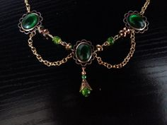 This is a handcrafted choker made from gold plated findings and bottle green German glass cabochons and beads, there is an extender chain and