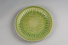 Plat du Longquan à marli polylobé en épaisse porcelaine décorée en incision d'un kilin céleste flottant sur des nuages tsi sous couverte monochrome céladon vert olive au centre et de godrons rayonnants au marli incisés de motifs floraux.  Chine. Dynastie Yuan. 1279 à 1368
