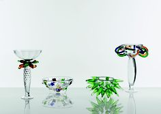 ANGELA clear glass stand with yellow, red, green and blue decoration. OLGA clear glass centrepiece with  green, blue, yellow and red decorations. PINO clear and green glass centrepiece. PROUNIER clear glass centrepiece with coloured fl ower-shaped decorations.