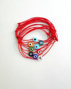 Wearing a thin scarlet or crimson string as a type of talisman is a Jewish folk custom as a way to ward off misfortune brought about by the evil eye. It is worn as a bracelet or band on the left wrist of the wearer (understood in some Kabbalistic theory as the receiving side of the spiritual body). Evil Eye Ring, Evil Eye Bracelet, Red String Of Fate, Evil Eye Charm, Spiritual Gifts, Ribbon Bows, Glass Beads, Type, Scarlet