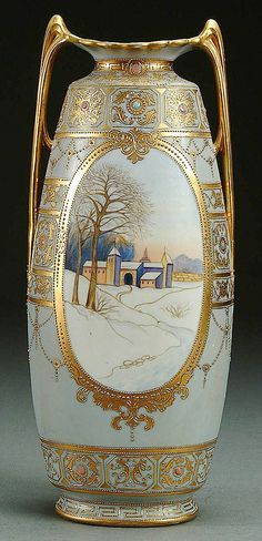 A NIPPON WINTER SCENIC DECORATED PORCELAIN VASE CIRCA 1915 WITH HAND PAINTED SCENE OF A SOWY MONASTERY WITHIN A GILT CATOUCHE WITH ENAMELED JEWELS