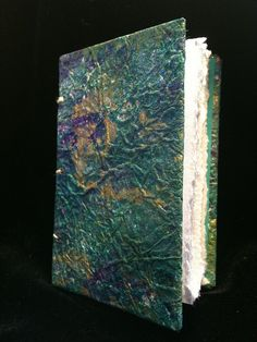 """Miniature (3""""x2"""") Coptic-bound journal with three signatures. The covers feature a decorative paper I made using acrylic paints and a distressed brown paper shopping bag."""