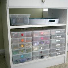 all of my embellishments. They are in plastic compartmentalized boxes ($1.95 ea. from Wal-mart) by color. It is amazing how much stuff these things can hold once you start taking emellishments out of their packaging! Just above the embellishments is a little shelf that has a tray where I like to toss my scraps. There is also a platic box that holds all of my Palette Ink pads.