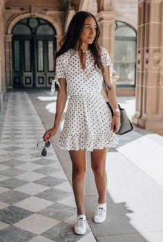 Vestido curto branco com poá, tênis branco, bolsa preta