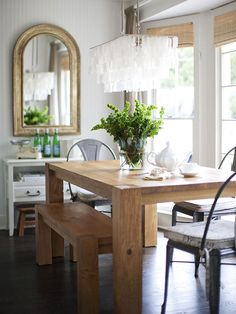 Beauty in the Details - A large wooden dining table warms up the all-white space and looks right at home in front of a bank of windows. The large gold-framed mirror reflects the natural light streaming in and adds an element of elegance
