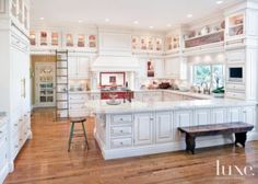 The kitchen's English manor-style cabinetry from Clive Christian, matched with veined granite countertops from Saban Tile Marble and Granite, gets an updated look with a subway tile backsplash from Waterworks; a rolling ladder provides access to the vitrine.