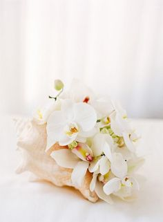 Pretty seashell centerpiece. (designed for a wedding) I would use it for any beach themed party, just change the flowers up.