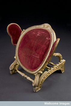 Bed rest, adjustable, England, c.1720. plaster & wood with padded red velvet supports. Used in a hospital or at home to support a person who had been confined to bed – perhaps for medical reasons. Has 6 different positions & is adjusted using a ratchet, the set of teeth on the edge of the support bars ensures the rest stays in position. The arm supports are also adjustable. Judging from the quality of the materials and design, the rest was used by a wealthy person. Wellcome Images. Ref: A602069