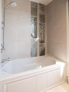 The bathtub has a neutral wall tile surround that brings serenity and ...