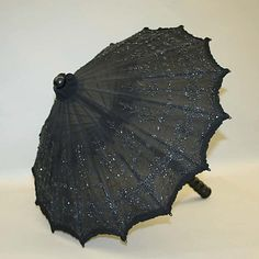 Parasol  Date:     ca. 1885 Culture:     American Medium:     silk, wood, metal Dimensions:     Length: 26 3/4 in. (67.9 cm) Credit Line:     Gift of Francesco de'Rogati in memory of Irma Catani de'Rogati, 1983 Accession Number:     1983.110