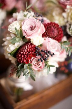 Bouquet of crimson and white dahlia, soft pink and ivory roses, viburnum berry with foliage.