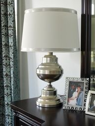 Trash to Treasure - Brass lamp from Goodwill sprayed with Krylon Premium Silver Foil Metallic, then lightly sprayed with Gold Metallic for a tarnished silver effect.  The white Target shade was embellished with silver ribbon.