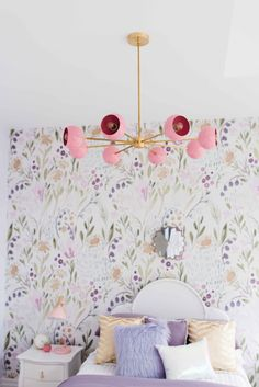 Feminine and floral girl's bedroom made over with pink and lavender wallpaper and a glam pink and brass chandelier.