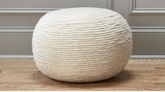 Could be cute as an ottoman or tucked under a coffee table part way for transitional seating /ottoman use - wool wrap pouf