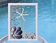 Beach House Decor Coastal. 2017 Interior Design Trend. Beach Wall Art. Ocean Decor. Glass Wall Art. Best Sea Glass Art Window. Beach Glass Windows. Seaglass Windows. Best Coastal Wall Art Decor. Best Gift for Her. Best Gift for Him. Flat Rate Shipping.  A hand crafted sea glass art window. A neutral design using mussel sea shells, miniature sea shells and white sea glass. It is moisture resistant: you may place it in your patio area (as long as it is covered by a roof) or in your bathroom…