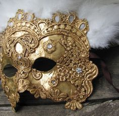gold mask with white feather