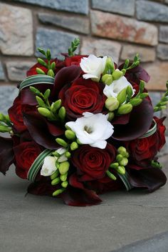 a beautiful bouquet of burgundy Roses, black Calla Lilies, and white Freesia