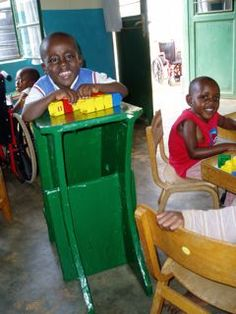 This is a happy child in Rwanda using Adapted Cardboard Equipment made by UK-based People Potential. Using old cardboard boxes means that money can be saved to spend on the necessary metal and electronic assistive devices such as wheelchairs and hearing aids. Expensive tools are not necessary. APT (Assistive Paper Technology) can be done in the home using kitchen knife.