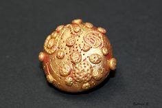 Brosche rot/gold schimmernd aus Polymer Clay.    Polymer Clay ist eine ofenhärtende Modelliermasse, die es in verschiedenen Farben gibt. In rohem Zust