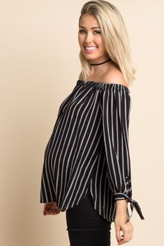 A striped off shoulder maternity top. Long sleeves with sleeve tie details. Rounded hemline with slit sides. This style was created to be worn before, during, and after pregnancy.