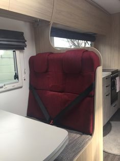 This motorhome dinette seat doubles as passenger seating. It has a feature back in ruby red. Motorhome Interior, Comfort Mattress, Geometric Fabric, Fabric Houses, Roman Blinds, Blinds For Windows, Ruby Red, Soft Furnishings, Vehicle
