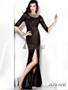 Evening Gowns by Jovani, style 834. This sophisticated long velvet gown is stunning in classic black. The high scoop neck features a jeweled neckline and sheer panel and 3/4 gathered sleeves. A keyhole accents the high back. A long slim skirt has a side front slit finishes with a back train. Shown in Black.