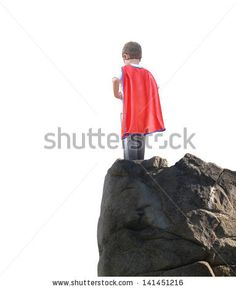 A young super hero boy is wearing a red cape and standing on a rocky cliff looking at a white isolated background for copyspace. by Angela Waye, via Shutterstock