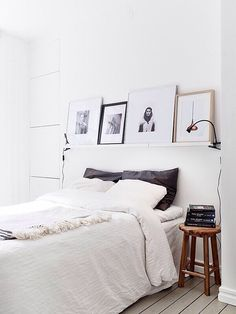 simple white bedroom with shelf over the bed with leaning framed art