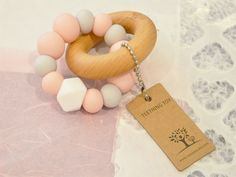 A Pastel Pink Nature Bubz Teething Toy is a most stylish gift for a baby girl. The pink and grey chewable silicone beads are BPA free and interlocked with a smooth beech wooden ring. Parents and babes will love this present. $21.95