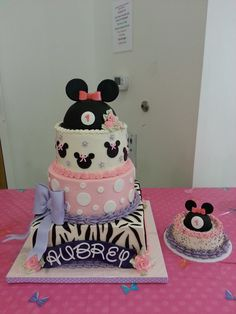 "Disney Themed Cakes - * Minnie Mouse first birthday cake. White cake with Swiss meringue buttercream, and fresh strawberries and glaze between each tier. 12"" square, 10"" round, 8"" round, half ball pan for the hat, 6"" smash cake, and mini ball pan for hat on the smash cake."
