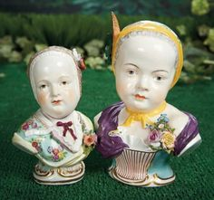 """Two German Porcelain Busts with Elaborately Painted Bonnets~~~6"""" (15 cm.) -8"""". Each is porcelain bust of child with slightly inclined head and well-detailed painting of features, having sculpted cap and bodice, with applied details of flowers, bows, and feathers, and each having fancily painted bodice with Dresden floral decorations and ribbons. Germany, circa 1900."""