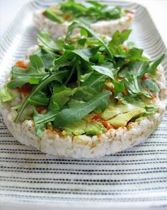 Perfectly ripe avocado, Handful of arugula, Sriracha, Lightly salted rice cakes. DIRECTIONS : Spread avocado across rice cake. Drizzle desired amount of Sriracha. Dice arucula into smaller pieces. Top each rice cake with arugula and enjoy.